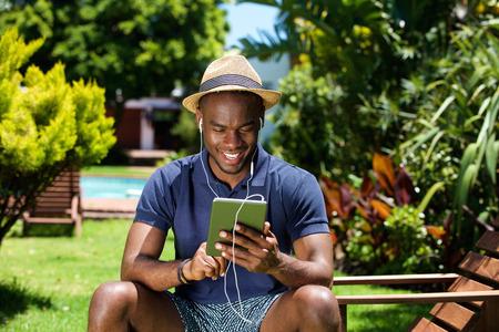 auriculares: Retrato de un hombre africano joven sonriente que se sienta al aire libre usando la tableta digital Foto de archivo