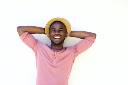 hands behind head: Close up portrait of a young black man laughing with hands behind head on white background