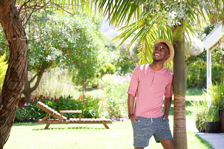 black guy: Portrait of happy young african man leaning to a tree outdoors on a summer day