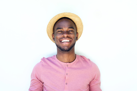 guy standing: Close up portrait of a smiling young black guy with hat against white background
