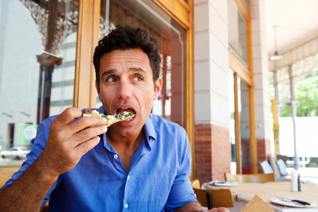 Portrait of an older handsome man eating pizza at outdoor restaurant
