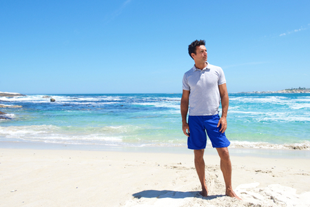 Portrait of a fit middle aged man standing barefoot at the beach