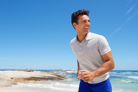 Portret van een gelukkige man van middelbare leeftijd lopen op het strand