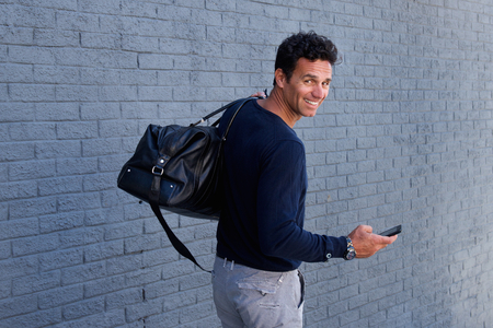 turn back: Portrait of man walking with mobile phone and bag turning and smiling Stock Photo