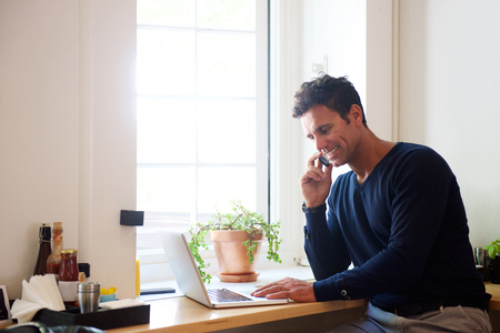 Portret van een man met behulp van mobiele telefoon met laptop in cafe Stockfoto
