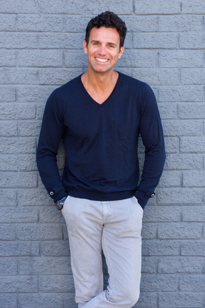Portrait of a confident man smiling against gray wall