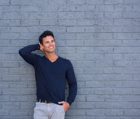 Retrato de un hombre maduro guapo sonriente con la mano en el pelo contra el fondo gris