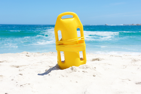 life saving: Yellow life saving buoy in sand at beach