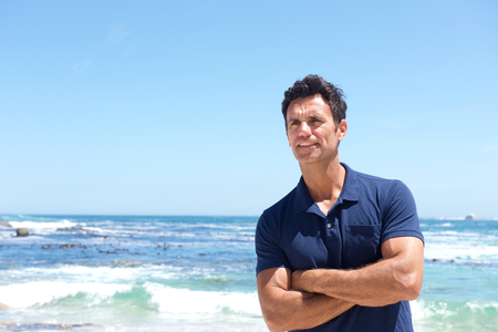 Portrait of rugged middle aged man standing at the beach Stock Photo
