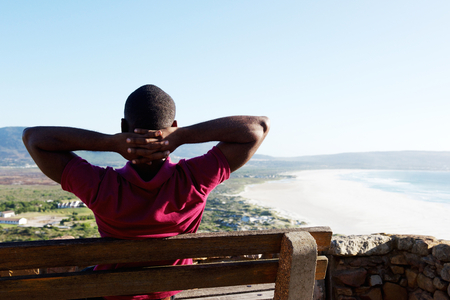 hands behind head: Rear view portrait of young african man sitting relaxed on a bench with his hands behind head, young guy on vacation. Stock Photo