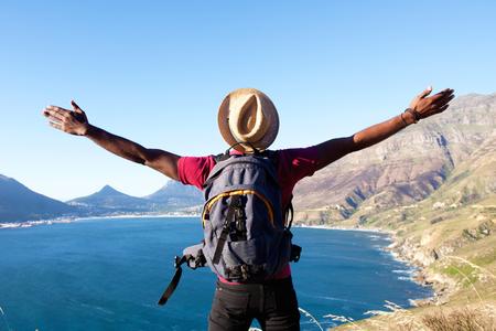 Achteraanzicht portret van een jonge man met rugzak staande op een berg met open armen verspreid Stockfoto