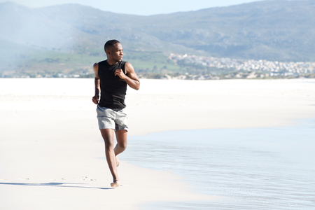 Portrait of healthy young african man running on the beach in summer