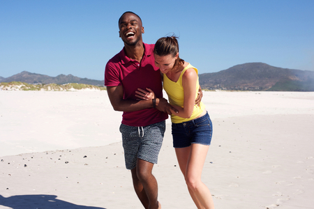 black guy: Portrait of happy young couple in love walking together on beach Stock Photo