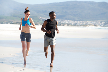 young adult woman: Full length portrait of healthy young man and woman running together along the beach