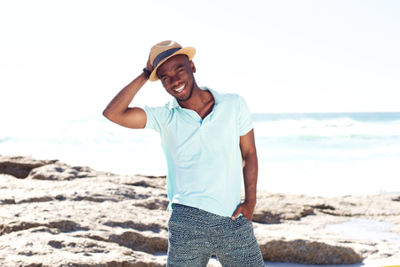 cool guy: Portrait of cool young guy with hat smiling at the beach in summer