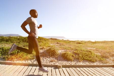Portret pełnej długości boku siłowni człowiek pracuje na Boardwalk na plaży w jasny słoneczny dzień Zdjęcie Seryjne