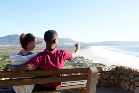 man sit: Rear view portrait of young couple sitting on a bench with man pointing at the sea, young couple on vacation. Stock Photo
