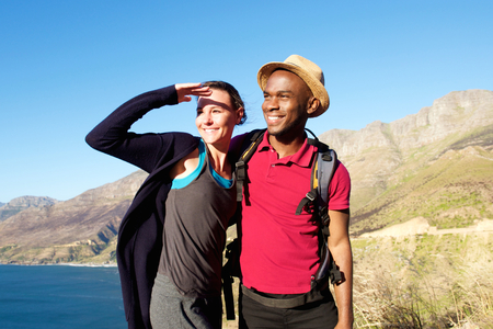 mixed races: Portrait of happy young mixed race couple on summer holiday standing together outdoors and looking away at a view Stock Photo