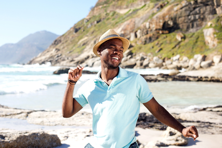 casual fashion: Portrait of young african man dancing at the beach on summer day Stock Photo