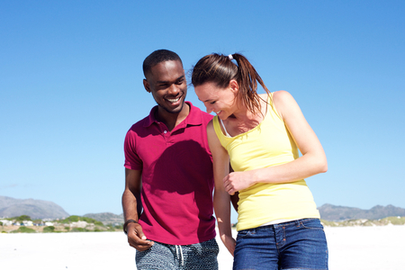 black man white woman: Portrait of smiling young couple walking together on the beach Stock Photo
