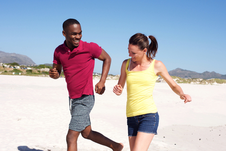 black couple: Portrait of happy young couple running together on beach