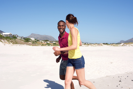 black couple: Side portrait of young couple running together on seashore Stock Photo