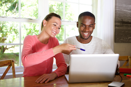 Portrait de jeune couple heureux assis à une table et utilisant un ordinateur portable ensemble
