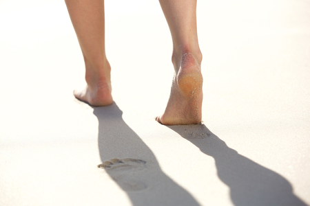 sandy feet: Closeup of woman walking on sandy beach leaving footprints in the sand Stock Photo