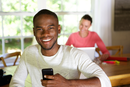 happy african: Close up portrait of smiling young african man with mobile phone and woman sitting in background