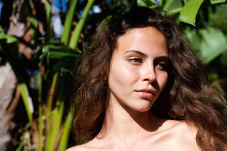 Caucasian woman: Portrait of a beautiful woman outdoors with bare shoulders looking away
