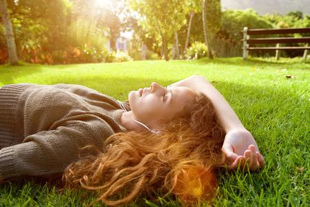 terreno: Ritratto di una giovane donna attraente disteso sul prato ascoltare la musica