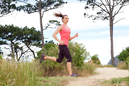dirt path: Full length portrait of sporty woman running on dirt path outdoors