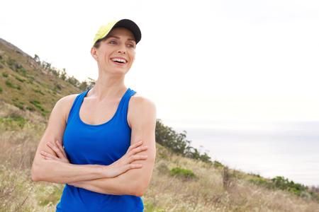 atletismo: Retrato de risa mujer atlética con los brazos cruzados de pie por mar fuera en ropa deportiva