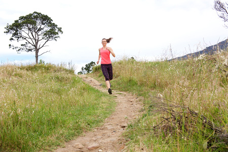 dirt path: Full length portrait of athletic woman running on dirt path outdoors in park Stock Photo