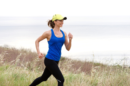 natural setting: Side portrait of smiling athletic woman jogging on trail outside in natural setting by the sea in a baseball cap