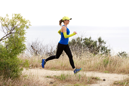 dirt path: Full length side portrait of sporty woman running on dirt path
