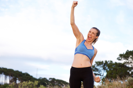 excited woman: Portrait of excited sports woman cheering with arms raised Stock Photo