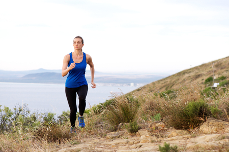 Full length portrait of woman running up hill with sea in background Banque d'images