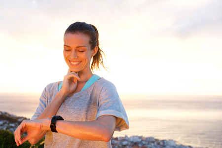 healthy looking: Close up portrait of fit woman timing her heart rate with watch Stock Photo