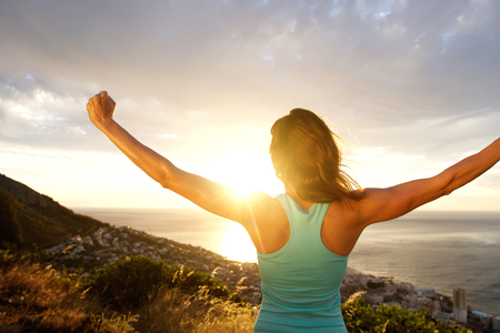 fit: Portrait of woman from behind stretching out her arms in front of sunrise