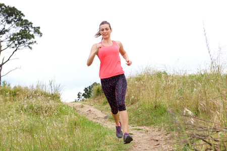 dirt path: Full length portrait of sporty woman running on dirt path outdoors in park