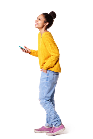 Plein portrait du côté du corps de la fille afro-américaine debout avec un téléphone cellulaire sur fond blanc
