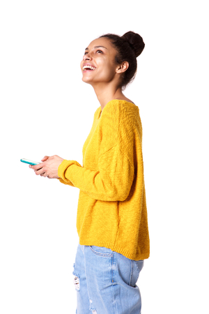 girl looking up: Side portrait of happy young woman with mobile looking away on white background