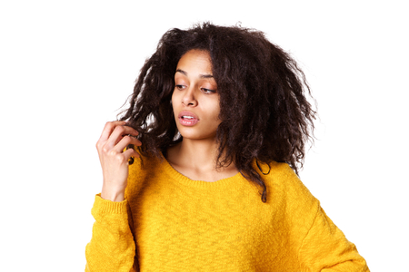 Close up portrait of young african woman holding damaged dry hair and looking sad on white background