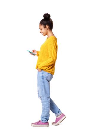 歩くと白い背景の上に携帯電話のテキスト メッセージを読んでリラックスの若い女性の完全なボディ側肖像画
