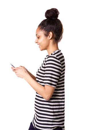 phone isolated: Side portrait of smiling young african woman using cellphone on white background Stock Photo