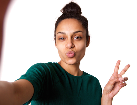 puckering lips: Portrait of young woman with puckering lips and peace hand sign taking selfie against white background Stock Photo