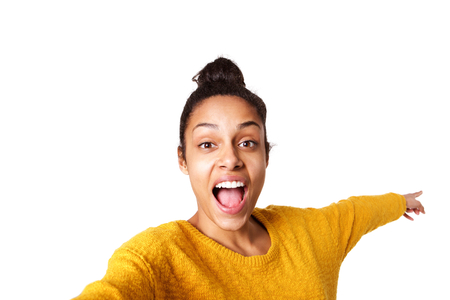 beautiful black woman: Close up portrait of excited young african woman pointing back and taking selfie on white background Stock Photo