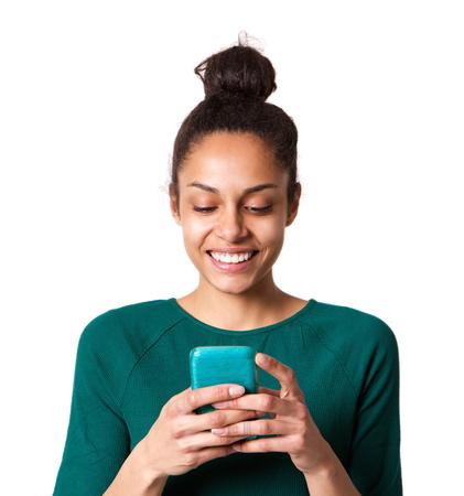 彼女の携帯電話にテキスト メッセージを読んで笑顔の若い女性の肖像画間近します。