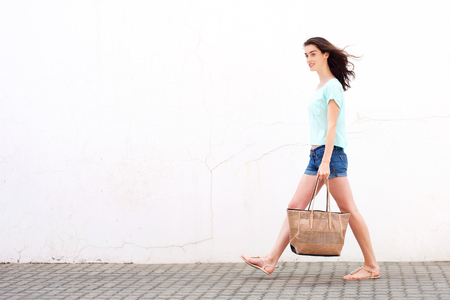 beautiful woman body: Full length side portrait of a smiling young woman walking with handbag